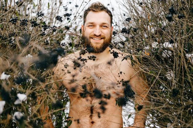 Porträt des ingwer lächelnden nackten mannes mit bart, der unter büschen aufwirft