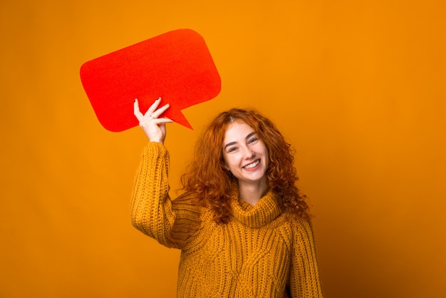Porträt des ingwermädchens, das kamera betrachtet und eine rote blasenrede hält, die über orange hintergrund steht