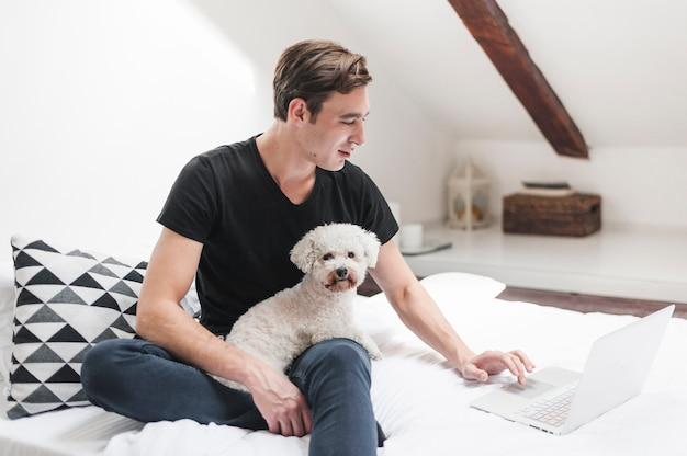 Porträt des inhabers mit seinem freundlichen hund, der zu hause laptop verwendet