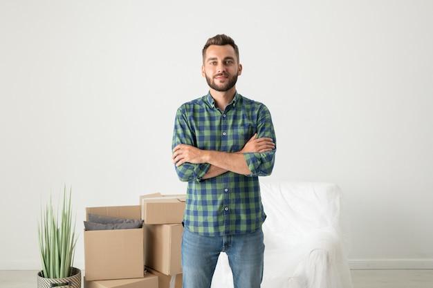 Porträt des inhalts hübscher junger mann im karierten hemd, das mit verschränkten armen in neuer wohnung mit beweglichen kisten steht