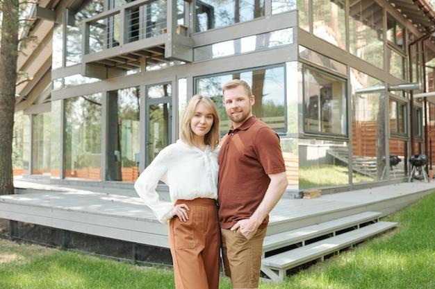 Porträt des inhalts zuversichtlich junges paar haben neues haus gekauft, das sich dagegen ausgibt