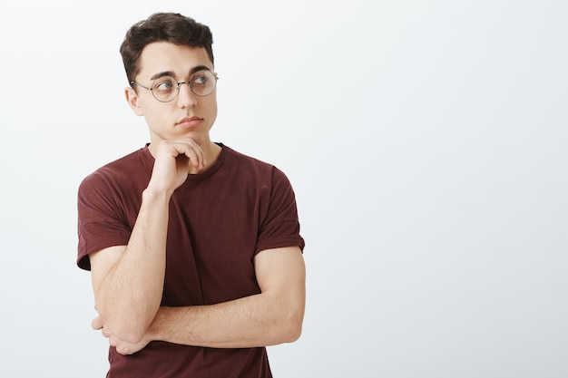 Porträt des intelligenten kreativen männlichen unternehmers im t-shirt und in der runden brille