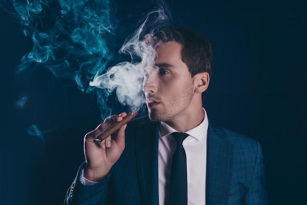 Porträt des intelligenten mannes, der weg raucht und zigarre hält