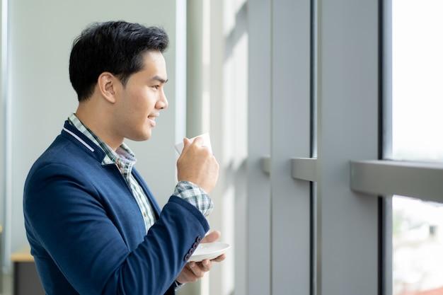 Porträt des intelligenten und hübschen jungen geschäftsmannes, der einen kaffee trinkt und oben außerhalb des fensterabschlusses schaut.