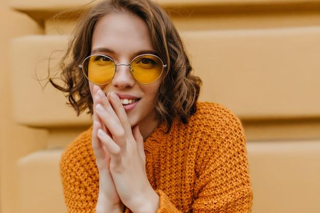 Porträt des interessierten hübschen weiblichen modells im warmen strickpullover