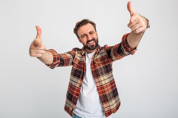 Porträt des isolierten lustigen kühlen gutaussehenden bärtigen mannes, der finger in der kamera zeigt