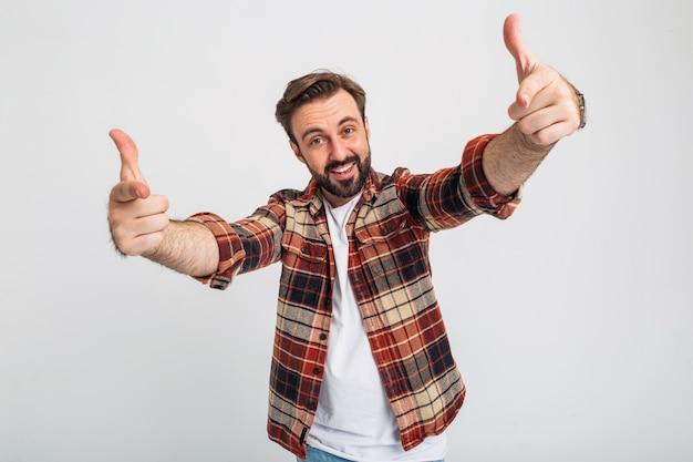 Porträt des isolierten lustigen kühlen gutaussehenden bärtigen mannes, der finger zeigt
