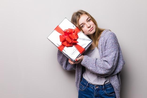 Porträt des jugendlich mädchens, das geschenk hält und innerhalb der box isoliert hört