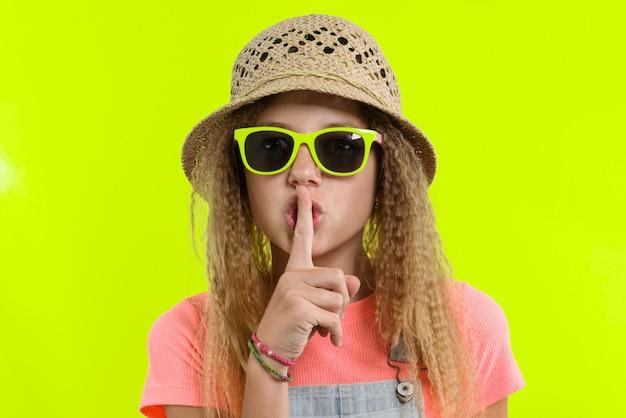 Porträt des jugendlich mädchens im sonnenbrillehut mit dem zeigefinger nahe den lippen, ruhezeichen zeigend
