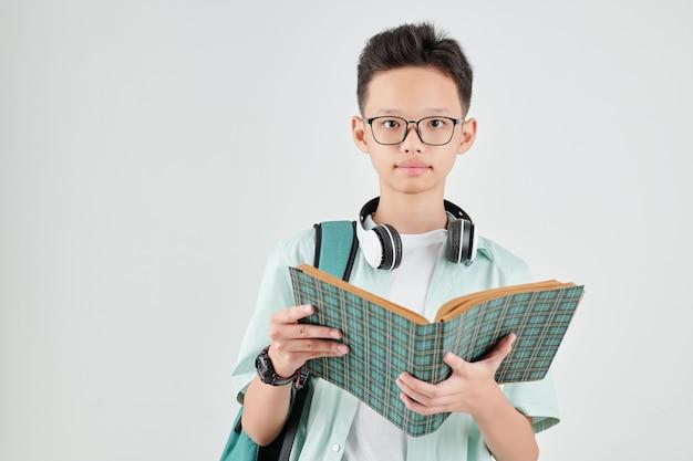 Porträt des jugendlichen asiatischen schuljungen in den gläsern, die mit geöffnetem buch stehen und schauen