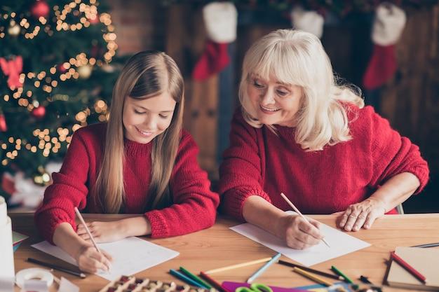 Porträt des jugendlichen enkels, das wunschbrief an den weihnachtsmann im dekorierten innenhaus schreibt