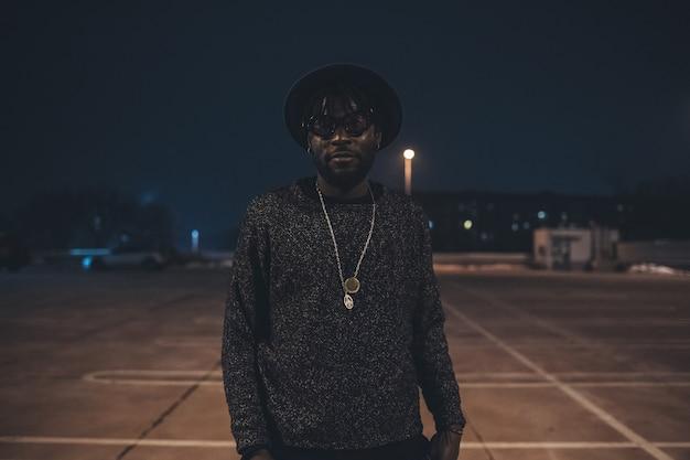Porträt des jungen afrikanischen mannes, der im parkplatz aufwirft