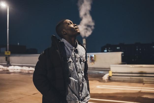 Porträt des jungen afrikanischen mannes, der in der straße steht und weiter schaut