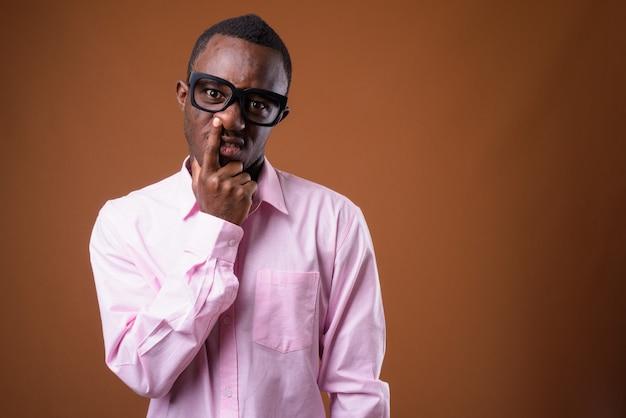 Porträt des jungen afrikanischen mannes, der seine nase aufhebt