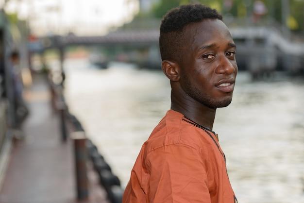 Porträt des jungen afrikanischen mannes, der traditionelle kleidung gegen ansicht des flusses in der stadt draußen trägt