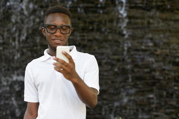 Porträt des jungen afrikanischen mannes gegen ansicht des gartens in der natur im freien