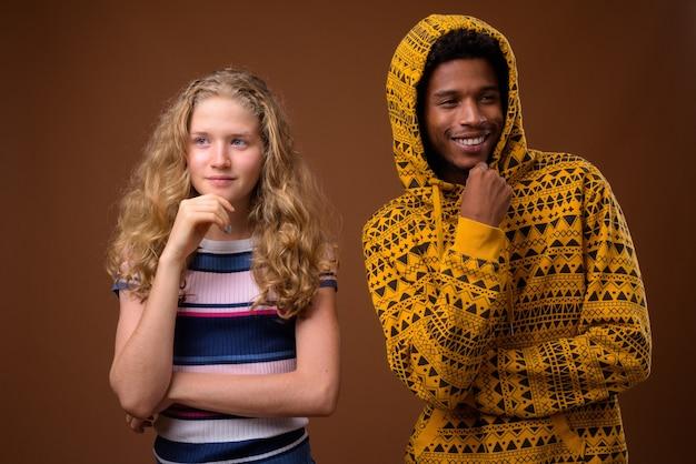 Porträt des jungen afrikanischen mannes und des kaukasischen teenager-mädchens denkend