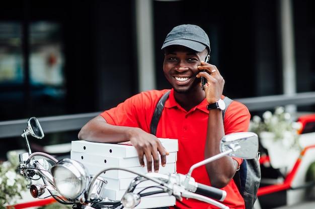 Porträt des jungen afrikanischen manns nimmt die bestellung telefonisch in motorradboxen mit pizza an und sitzt auf seinem fahrrad. urbaner ort.