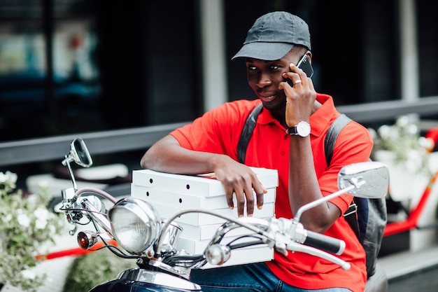 Porträt des jungen afrikanischen manns nimmt die bestellung telefonisch in motorradboxen mit pizza an und sitzt auf seinem fahrrad.