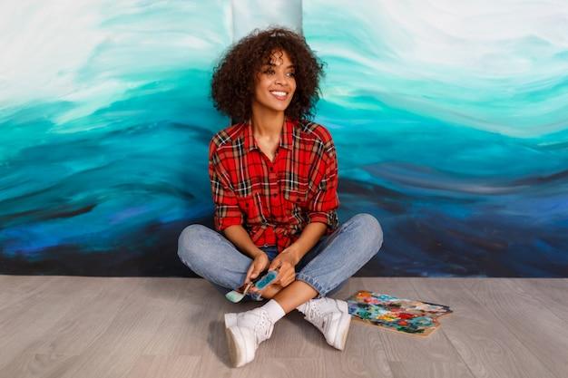 Porträt des jungen afrikanischen studenten, der mit erstaunlicher abstrakter handarbeit des abstrakten acryls im studio sitzt.