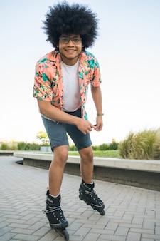 Porträt des jungen afro-lateinamerikanischen mannes, der kamera beim rollschuhlaufen im freien auf der straße betrachtet. sportkonzept. stadtkonzept.
