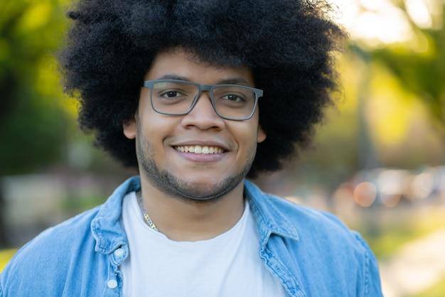 Porträt des jungen afro-lateinamerikanischen mannes lächelnd, während draußen auf der straße stehend. stadtkonzept.