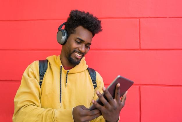Porträt des jungen afro-mannes, der sein digitales tablett mit kopfhörern benutzt