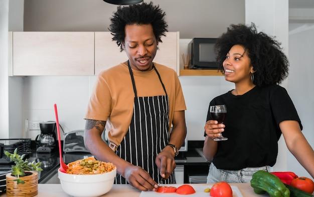 Porträt des jungen afro-paares, das zusammen in der küche zu hause kocht. beziehungs-, koch- und lifestyle-konzept.