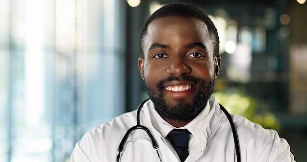 Porträt des jungen afroamerikanerarztes mit stethoskop, das kamera betrachtet und fröhlich lächelt. hübsches männliches arztlächeln. sanitäter im weißen kleid. drinnen.