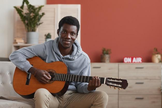 Porträt des jungen afroamerikanischen mannes, der akustische gitarre spielt und kamera betrachtet, während auf couch zu hause sitzen, raum kopieren