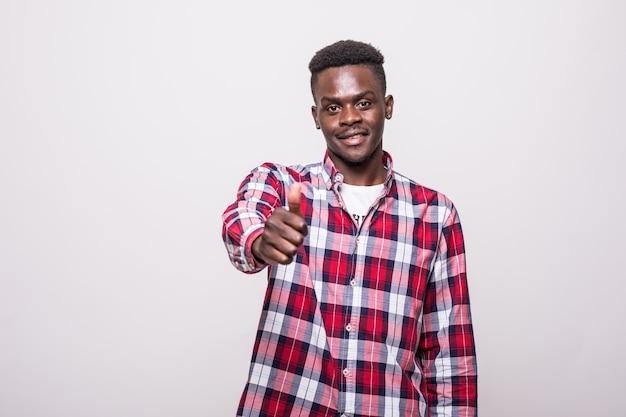 Porträt des jungen afroamerikanischen mannes, der daumen oben zeigt und lächelt,