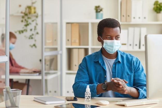 Porträt des jungen afroamerikanischen mannes, der gesichtsmaske trägt und hände desinfiziert, während er in der kabine am postpandemiebüro arbeitet