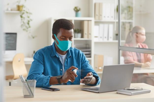Porträt des jungen afroamerikanischen mannes, der maske trägt, die hände desinfiziert, während am schreibtisch in der kabine am postpandemiebüro sitzen