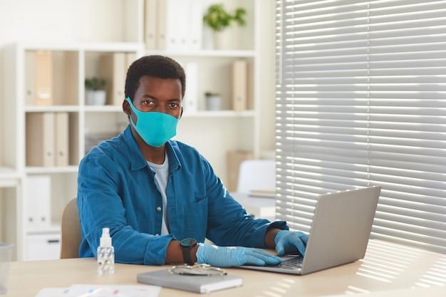 Porträt des jungen afroamerikanischen mannes, der maske und handschuhe trägt, die am schreibtisch im postpandemiebüro arbeiten