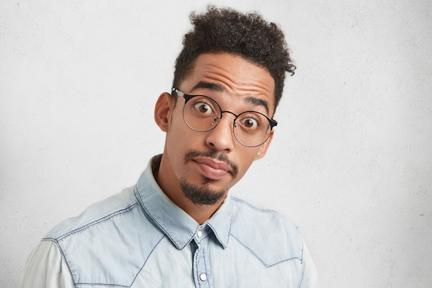 Porträt des jungen afroamerikanischen mannes mit abgehörten augen, hat trendige frisur, schnurrbart und bart, sieht verwirrt aus