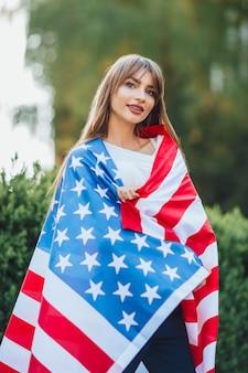 Porträt des jungen amerikanischen mädchens, das usa flahg hält
