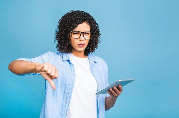 Porträt des jungen amerikanischen studentenmädchens mit dem gelockten afrikanischen haar, das digitale tablette hält und lächelnd steht über lokalisiertem blauem hintergrund
