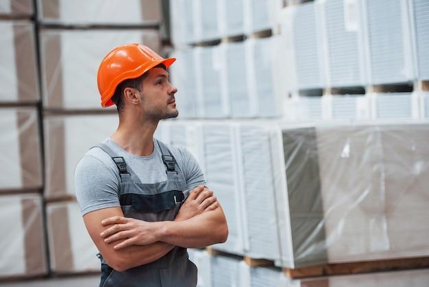 Porträt des jungen arbeiters in uniprom, der im lager ist.