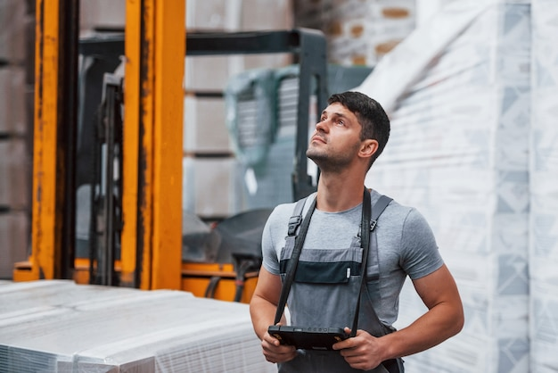 Porträt des jungen arbeiters in uniprorm, der sich im lager in der nähe von gabelstapler befindet.