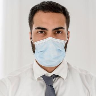 Porträt des jungen arztes, der eine medizinische maske trägt