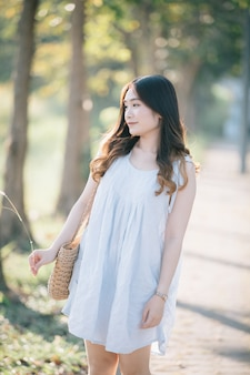 Porträt des jungen asiatinmädchenlächelns im blumengarten