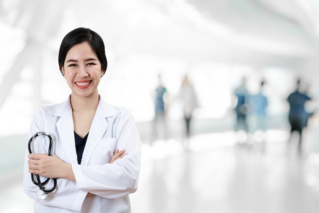 Porträt des jungen asiatischen doktors kreuzte die arme, die stethoskop halten