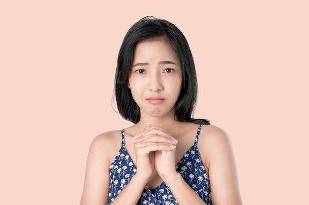 Porträt des jungen asiatischen frauenstirnrunzelngesichtes wird und die hände schreien, die gefaltet werden und hat etwas antrag.