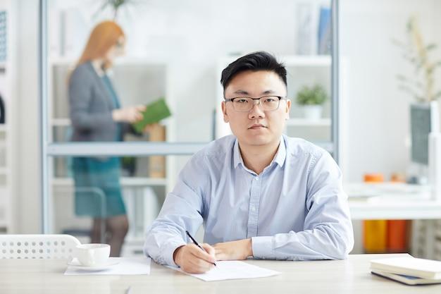 Porträt des jungen asiatischen geschäftsmannes, der brille trägt, während am arbeitsplatz in der bürokabine, kopienraum aufwirft