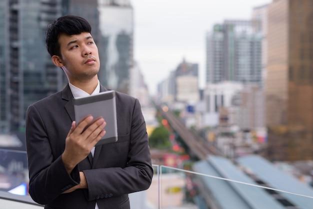 Porträt des jungen asiatischen geschäftsmannes, der digitales tablett gegen ansicht der stadt verwendet