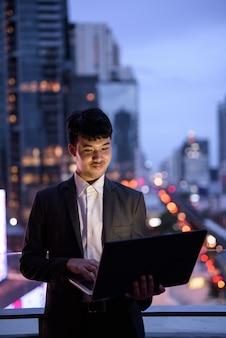Porträt des jungen asiatischen geschäftsmannes, der laptop gegen ansicht der stadt verwendet