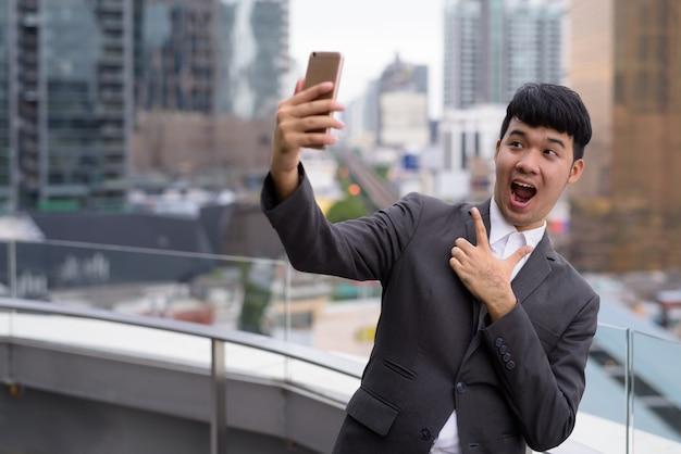 Porträt des jungen asiatischen geschäftsmannes, der telefon gegen ansicht der stadt benutzt