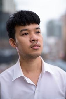 Porträt des jungen asiatischen geschäftsmannes gegen ansicht der stadt
