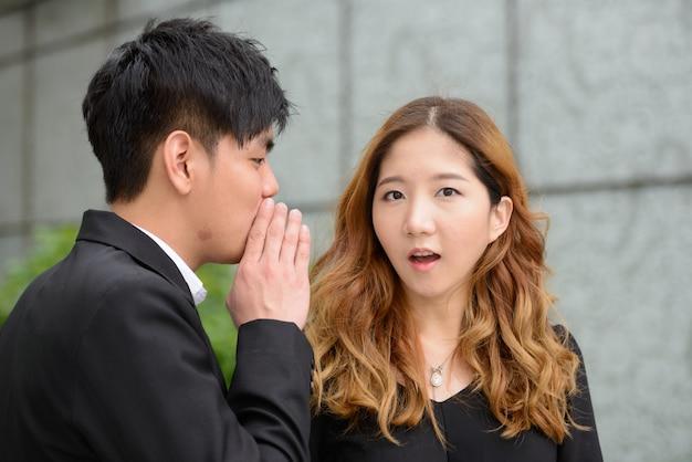 Porträt des jungen asiatischen geschäftsmannes und der jungen asiatischen geschäftsfrau zusammen in der stadt draußen