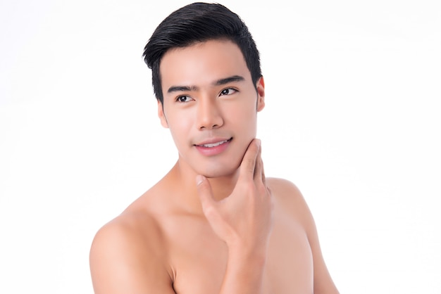 Porträt des jungen asiatischen gutaussehenden mannes mit der gesunden sauberen haut, die sein kinn lokalisiert berührt.
